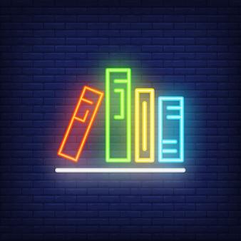 Libri sullo scaffale segno al neon. vari colorati in fila sullo scaffale. pubblicità luminosa di notte.