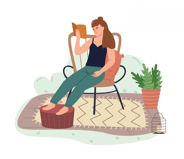Libro di lettura della ragazza in sedia comoda nel giardino