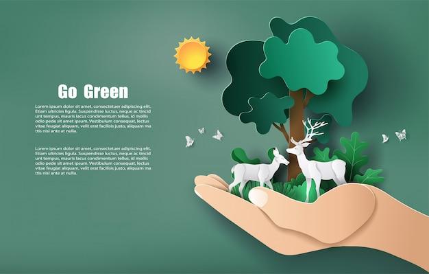 Lo stile di arte della carta della mano che tiene l'albero e le piante con cervi, salva il pianeta e l'energia.