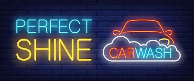 Lucentezza perfetta, testo al neon dell'autolavaggio con auto e schiuma