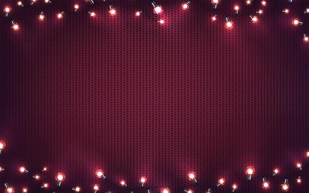 Luci di natale. ghirlande incandescenti di natale di lampadine a led sulla trama a maglia viola. sfondo vacanza