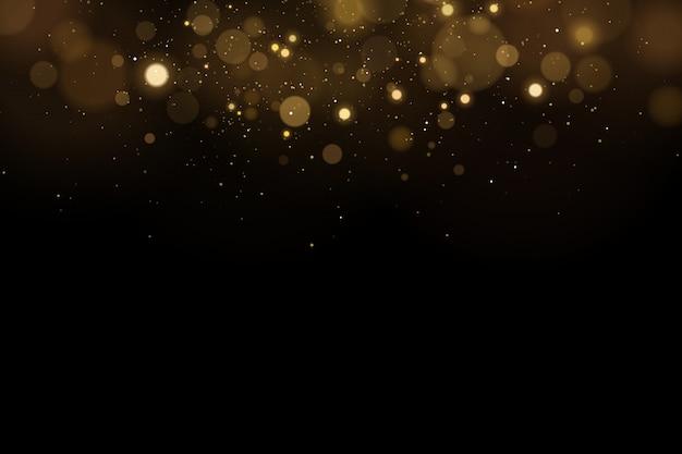Luci volanti magiche astratte con il bokeh dorato di riflessi su un fondo nero. effetto luce di natale.