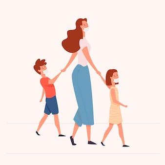 Madre che cammina con i suoi bambini che indossano maschere mediche