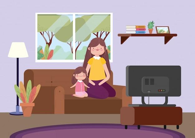Madre e figlia che si siedono in sofà che waching tv celebrazione felice di ringraziamento