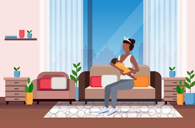 Madre l'allattamento al seno il suo neonato donna seduta sul divano con il bambino piccolo maternità nutrizione concetto di lattazione moderno salotto interno a figura intera