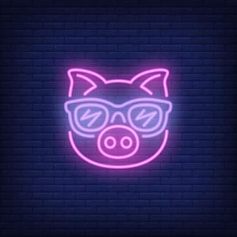 Maiale rosa simpatico cartone animato in occhiali da sole. elemento di segno al neon. pubblicità luminosa di notte.