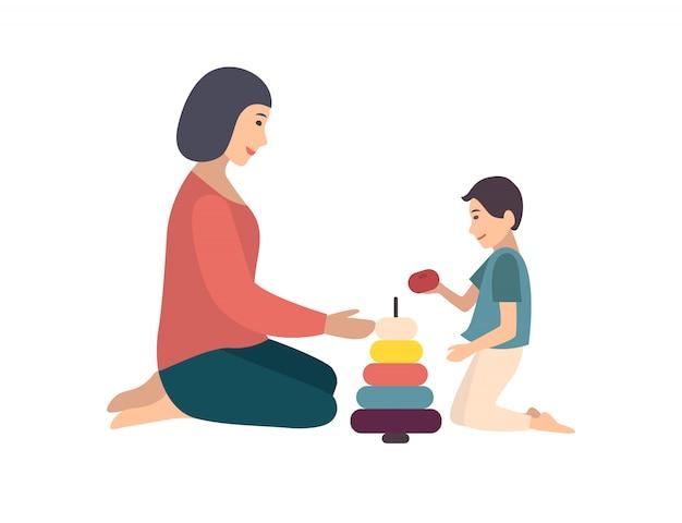 Mamma e figlio che si siedono insieme sul pavimento e che costruiscono piramide. madre che insegna al suo bambino a giocare con il giocattolo. personaggi dei cartoni animati divertenti isolati su fondo bianco. illustrazione piatta colorata