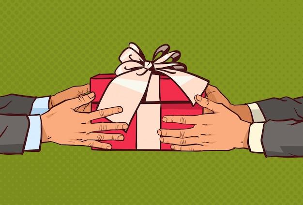Mani che danno regalo ad un altro saluto con la festa, scatola rossa presente con nastro e fiocco sopra vintage comico