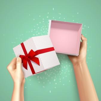 Mani che tengono il fondo realistico di vista superiore del contenitore di regalo con il cartone quadrato ed il raccordo rosso con l'arco