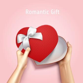 Mani che tengono la composizione realistica 3d di vista superiore del contenitore di regalo con il cartone a forma di cuore ed il testo editabile