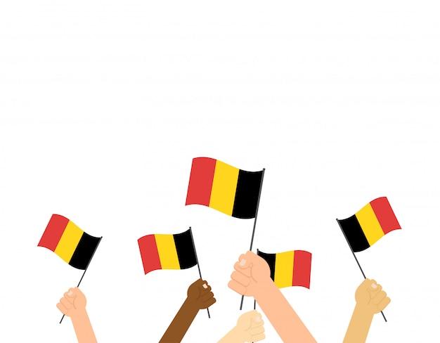 Mani che tengono le bandiere del belgio