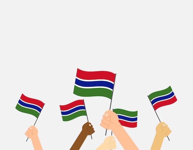 Mani che tengono le bandiere del gambia