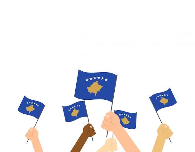 Mani che tengono le bandiere del kosovo