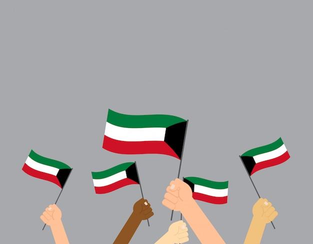 Mani che tengono le bandiere del kuwait