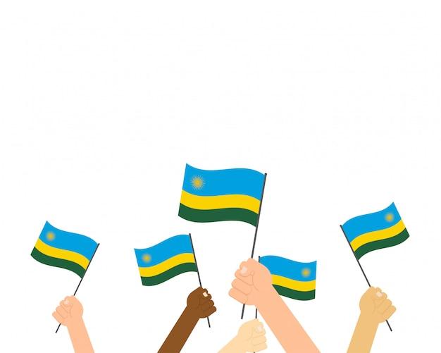 Mani che tengono le bandiere del ruanda