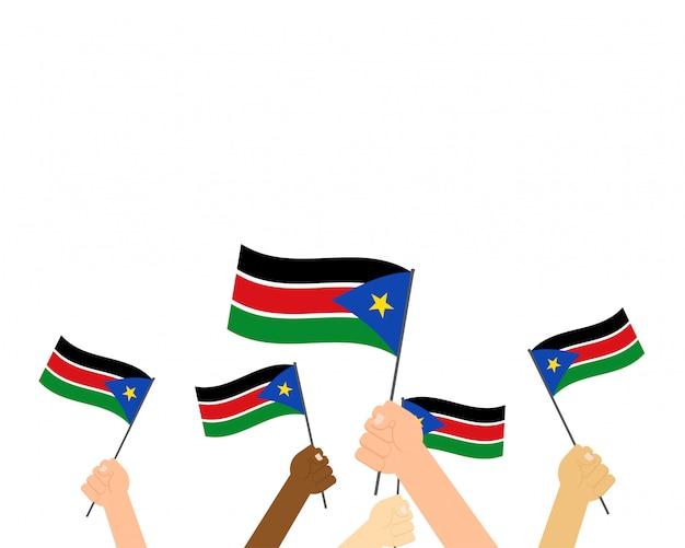 Mani che tengono le bandiere del sud sudan