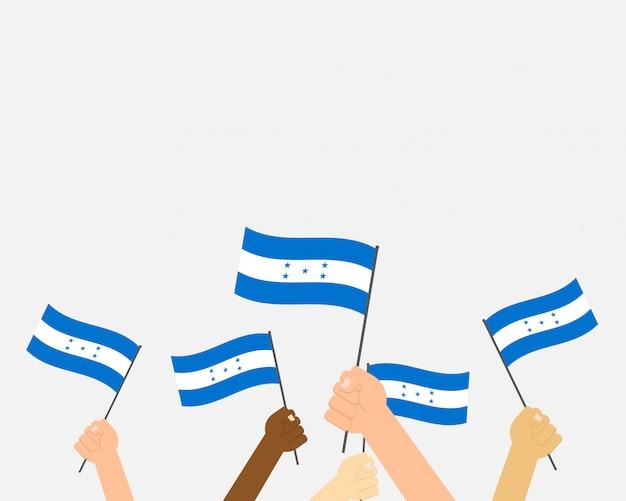 Mani che tengono le bandiere dell'honduras
