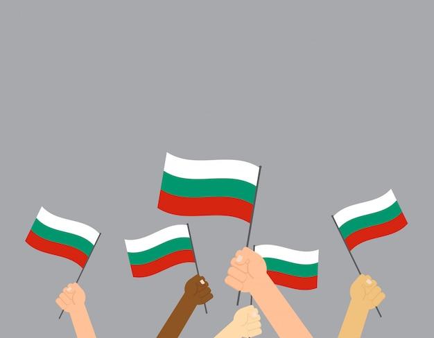 Mani che tengono le bandiere della bulgaria