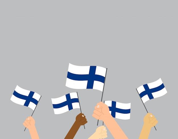 Mani che tengono le bandiere della finlandia