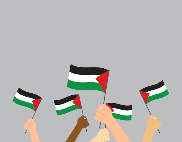 Mani che tengono le bandiere della palestina