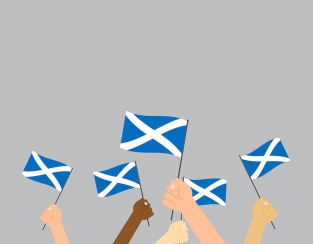 Mani che tengono le bandiere della scozia