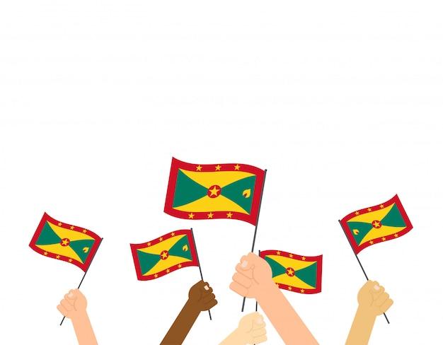 Mani che tengono le bandiere di grenada