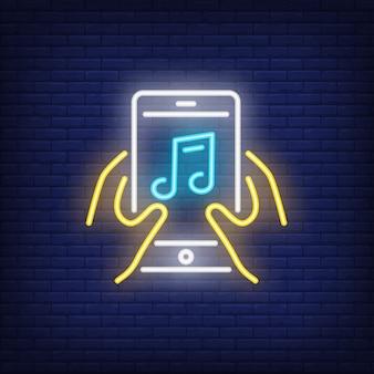 Mani che tengono smartphone con segno al neon di nota