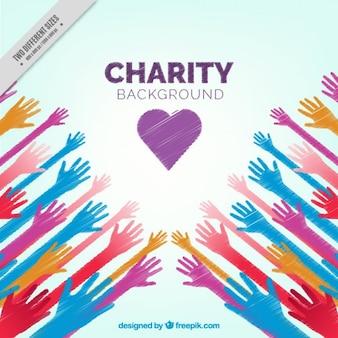 Mani colorate e uno sfondo di cuore di beneficenza
