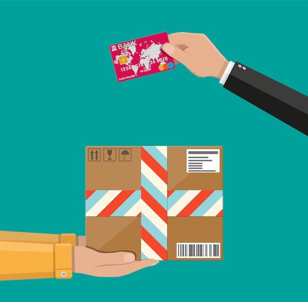 Mani con scatola di cartone postale e carta di credito
