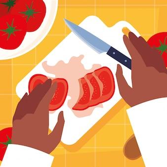 Mani del cuoco unico con il coltello e il bordo della cucina