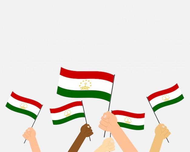 Mani dell'illustrazione di vettore che tengono le bandiere del tagikistan