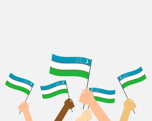 Mani dell'illustrazione di vettore che tengono le bandiere dell'uzbekistan