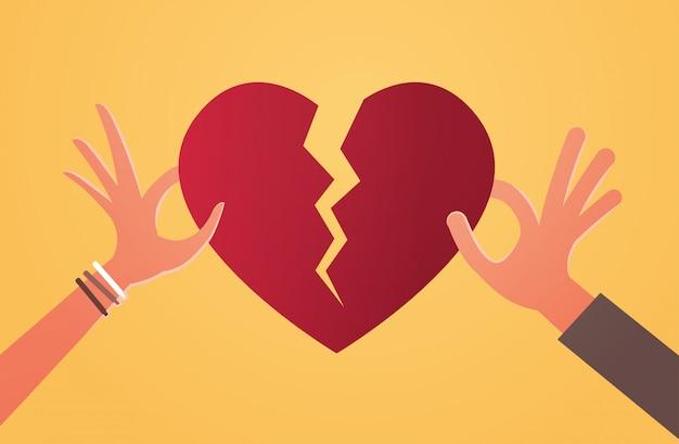 Mani di uomo donna che tengono pezzi di cuore spezzato