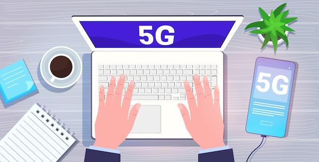Mani digitando sul computer portatile 5g rete di comunicazione online sistemi wireless connessione concetto quinta generazione innovativa di internet ad alta velocità vista dall'alto angolo sulla scrivania orizzontale