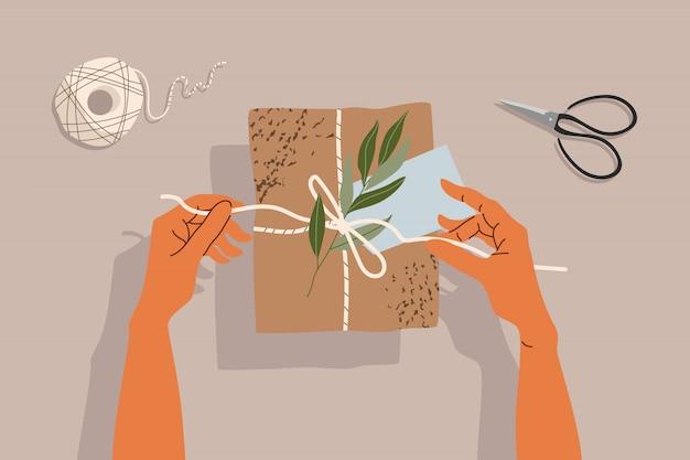 Mani e confezione regalo sul tavolo. illustrazione alla moda di mani, confezione regalo, forbici e ramo di un albero. sul tavolo, vista dall'alto in basso. illustrazione moderna disegnata a mano per web e stampa.