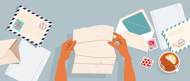 Mani in possesso di lettera. buste, francobolli postali e cartoline sul tavolo. vista dall'alto. banner illustrato moderno, carta. concetto di corrispondenza e consegna postale.
