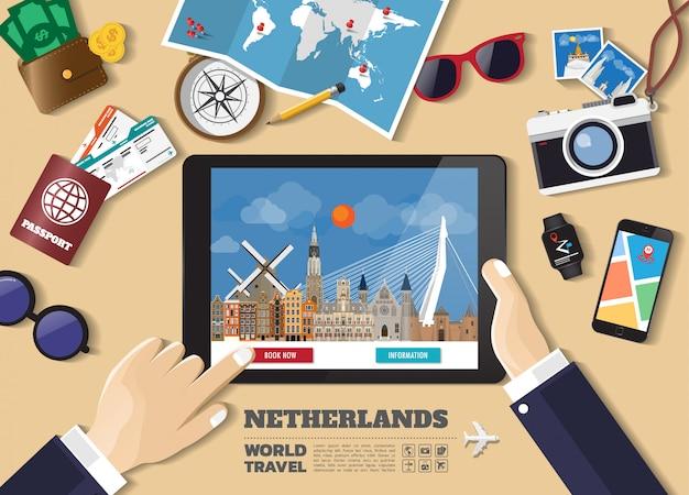 Mano che tiene destinazione di viaggio prenotazione smart tablet. luoghi famosi dei paesi bassi