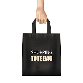 Mano che tiene la borsa della spesa shopping di tela nera alla moda