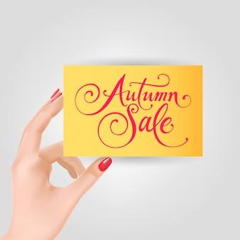 Mano che tiene la carta con lettering vendita autunno