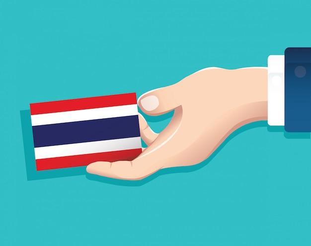 Mano che tiene la carta della bandiera della tailandia