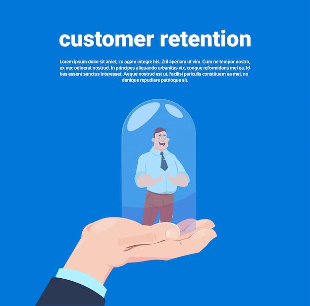 Mano del gestore della fidelizzazione del cliente che tiene un cliente in copertura una lampadina di vetro sopra fondo blu piano
