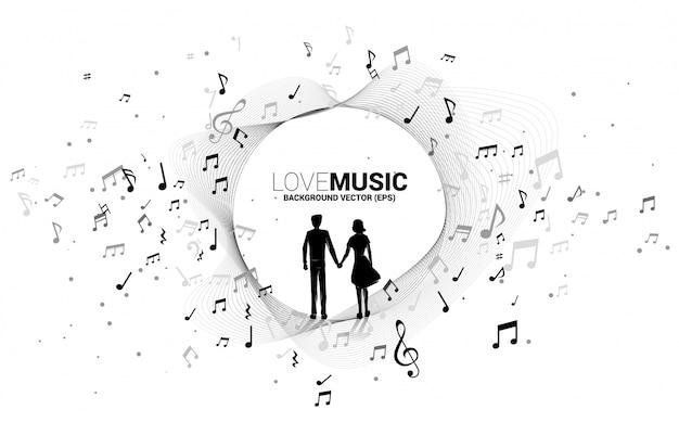 Mano della tenuta delle coppie dell'amante con flusso di dancing della nota di melodia di musica. sfondo di concetto per la canzone d'amore e il tema del concerto.