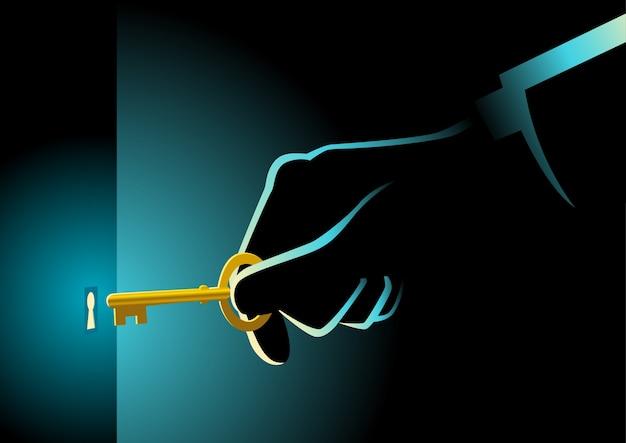 Mano di uomo d'affari che tiene una chiave d'oro