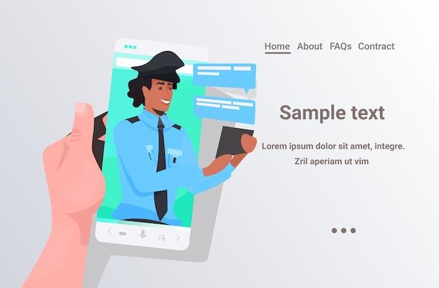 Mano umana utilizzando smartphone in chat con il poliziotto durante la videochiamata