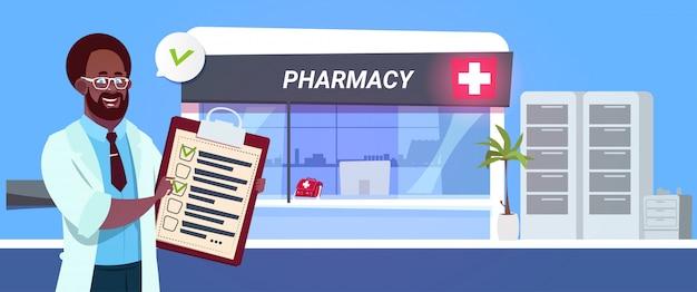 Medico afroamericano con la lavagna per appunti sopra il deposito della farmacia