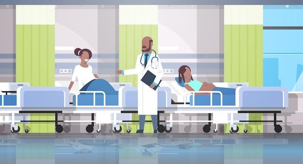 Medico maschio che visita e che esamina i pazienti delle donne incinte che si trovano nel letto di ospedale medico