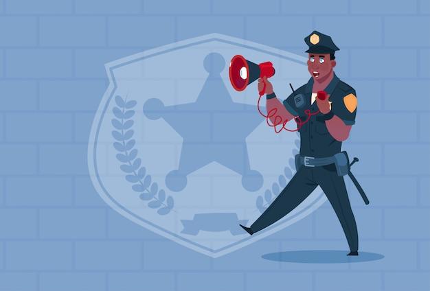 Megafono della tenuta del poliziotto afroamericano che indossa la guardia di uniforme uniforme sopra il fondo del mattone
