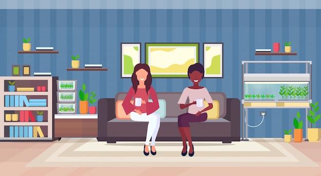 Mescolano le donne della corsa che si siedono sulle coppie dello strato che bevono l'interno moderno del salone dell'appartamento del caffè bevente con le piante della casa del contenitore di vetro elettronico domestico del terrario che coltivano il concetto orizzontale piano