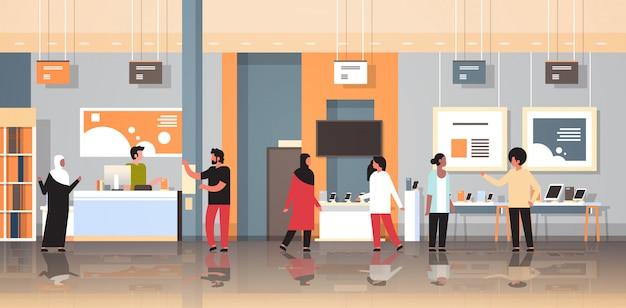 Mescolare i clienti della gara nel moderno negozio di tecnologia visitatori interni scegliendo il computer portatile schermo tv smartphone gadget elettronici mercato piatto orizzontale