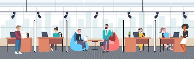 Mescolare i lavoratori della corsa nel concetto creativo del processo di lavoro del centro dello spazio aperto di lavoro creativo uomini d'affari e donne di affari all'orizzontale interno dell'ufficio dell'area di lavoro moderna del posto di lavoro